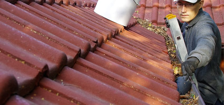 homeowner clearing gutters as part of spring home maintenance work